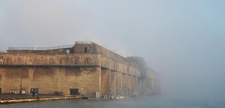 Le brouillard adoucit même les formes massives de la base sous-marine.