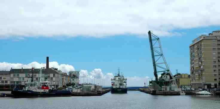 Un cargo sort du port de Saint-Nazaire, s'engage dans l'écluse sud et passe sous le pont levé.